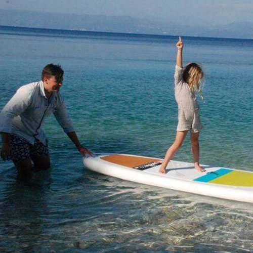 Sweet image of a little girl standing on a surf board on the sea being held by her father