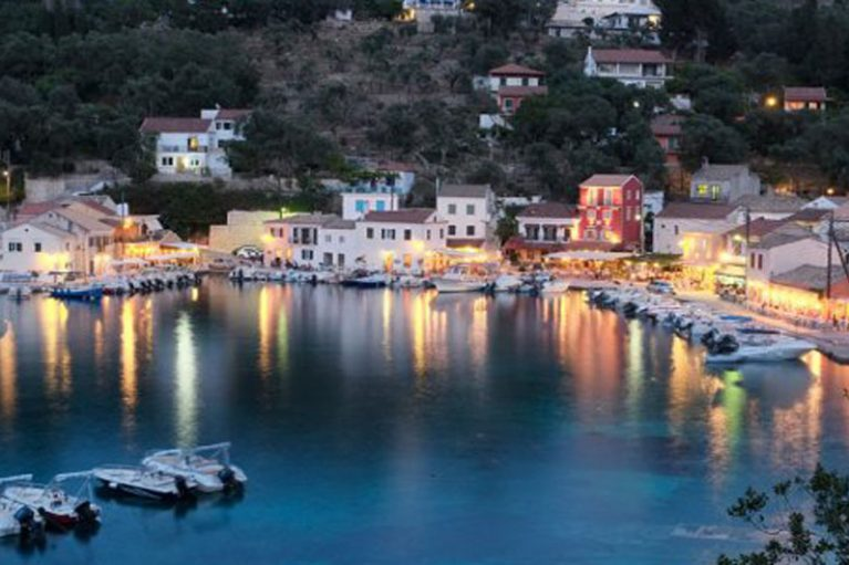 A stunning evening picture of Loggos in paxos showing all the lights from the boats reflected in the sea