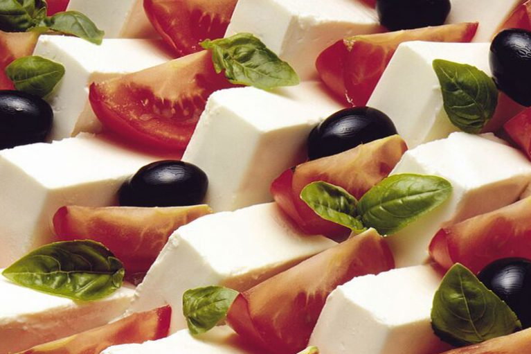 delicious looking salad of feta cheese, tomato and black olives with basil