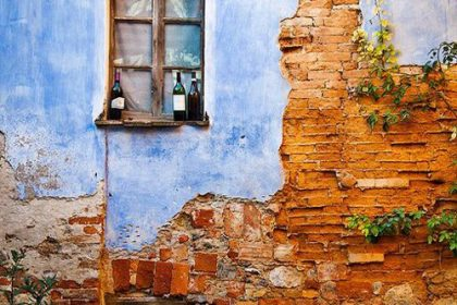 tumbledown wall with blue wash paint, beautiful window and some bottles of red wine