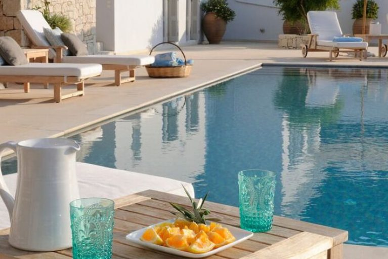 A beautiful shot of a pool at Ithaca Bay House in the Greek island of Ithaca. Plate of fruit in the foreground.