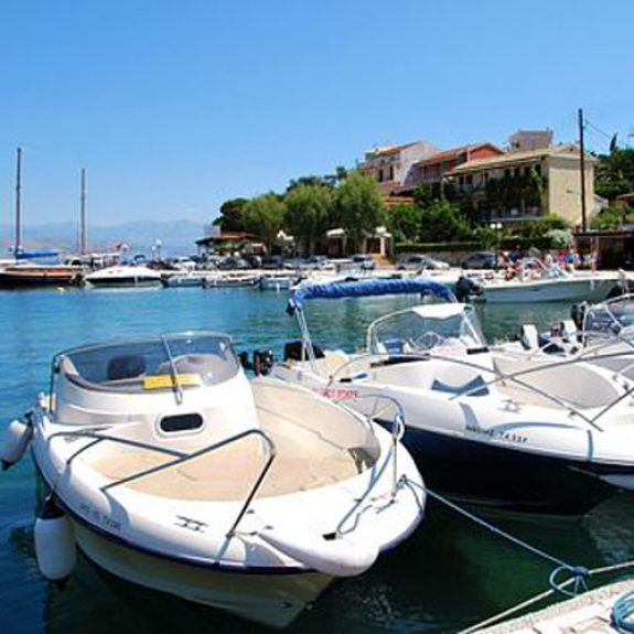 Boats bobbing about in the clear blue waters of Lakka in Paxos