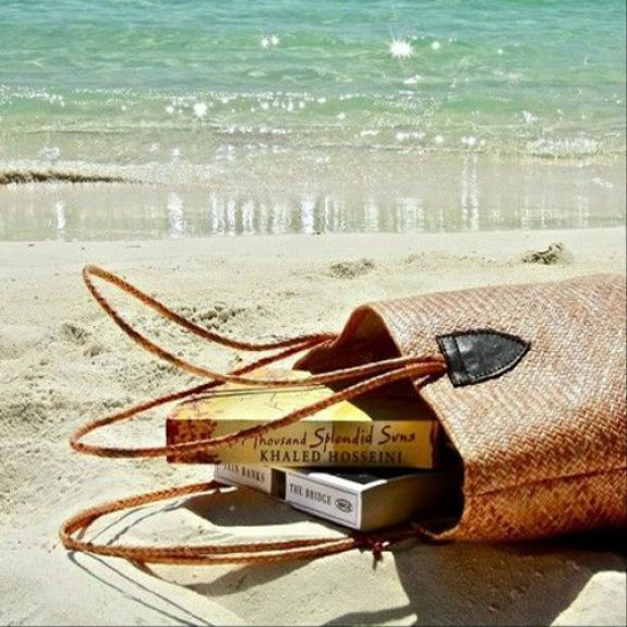 Image of a basket on the beach, the basket has tipped over on the sand and two paperback books have fallen out