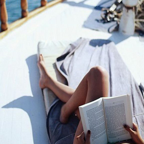 Image of a girl reading on a boat, her tanned legs are folded up and her book is open, the sea can be seen in the background