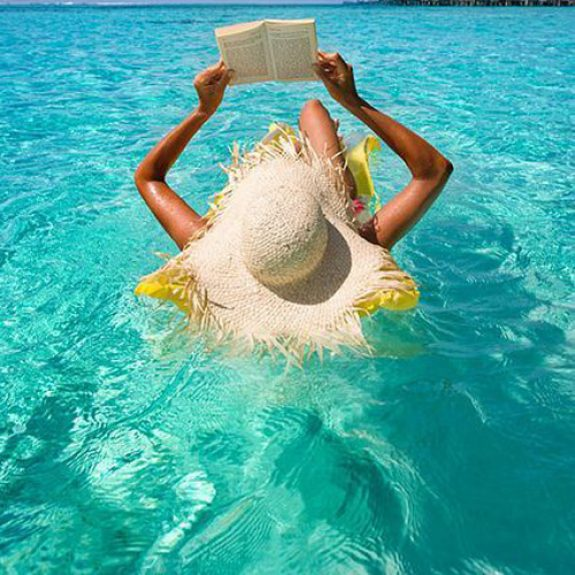 A girl floating on a lilo (unseen) in a swimming pool. She is reading a book with a huge straw sunhat on her head