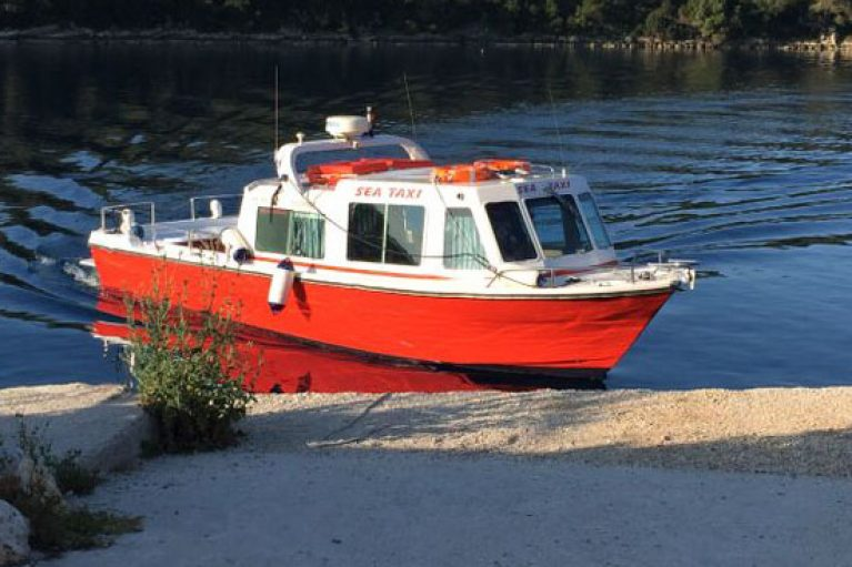 """alt=""""A picture of the little red and white boat that is the sea taxi based in Ithaca, the boat is bobbing on the Ionian sea"""""""