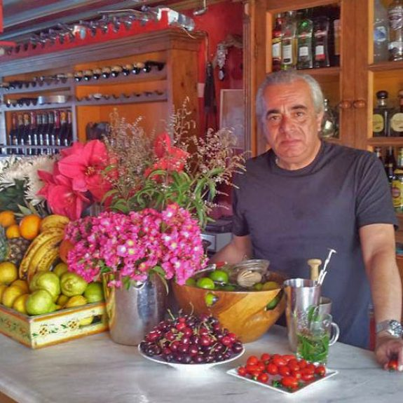 An image of Spiro Taxidi, the lovely barman at the bar in Loggos, Paxos. He is standing behind the bar surrounded by fruit and bottles