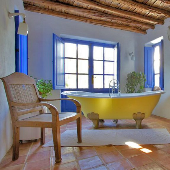 Image of a bright yellow free-standing bath in front of a blue window - in the bathroom at Finca Leonardo in Ibiza
