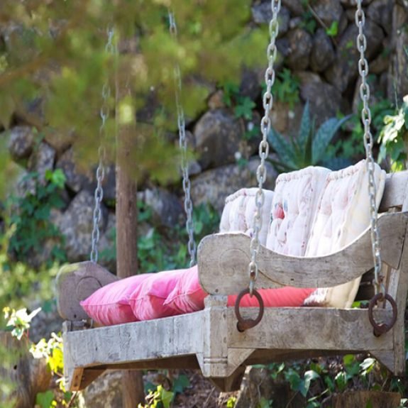 Image of a wooden swing seat at Finca Leonardo in ibiza, the seat has beautiful embroidered cushions on it and is hanging in a stunning garden