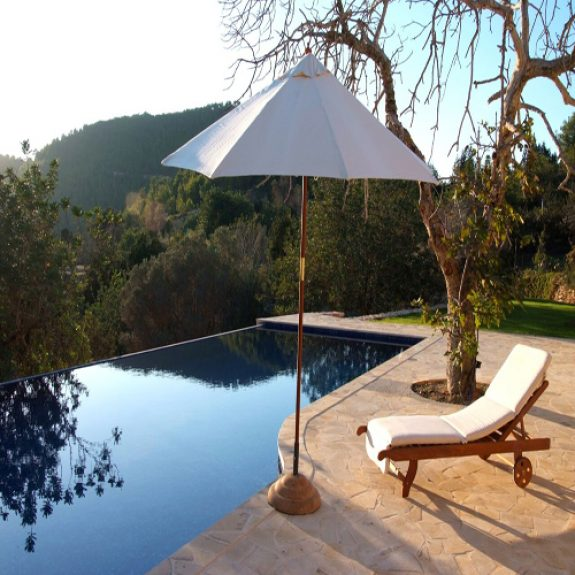 Image of the pool and a sun bed and umbrella at Finca 15 in Ibiza