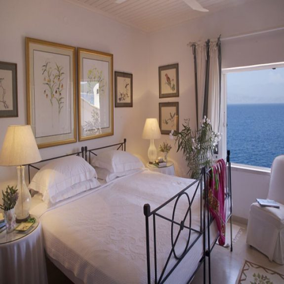 Image of bedrooms at Serenity House, Corfu. The room has an amazing view of the sea, the windows are open, the bed is white and there are lovely pictures on the wall above the bed