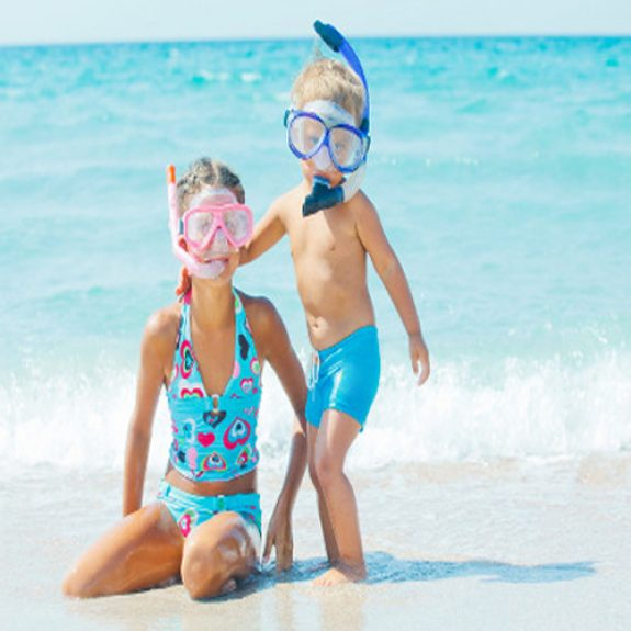 Image of two children wearing swimming masks sitting on the beach with blue sea in the background
