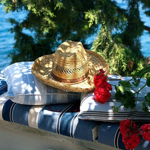 Image of straw hat sitting on a pile of striped pillows above the sea, there are red flowers also in the picture