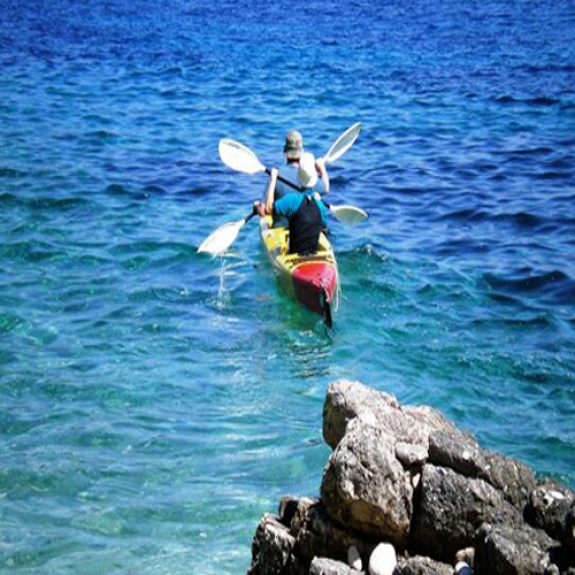 Image of 2 people in hats in a double kayak, paddling away with their backs to the camera, the sea is blue