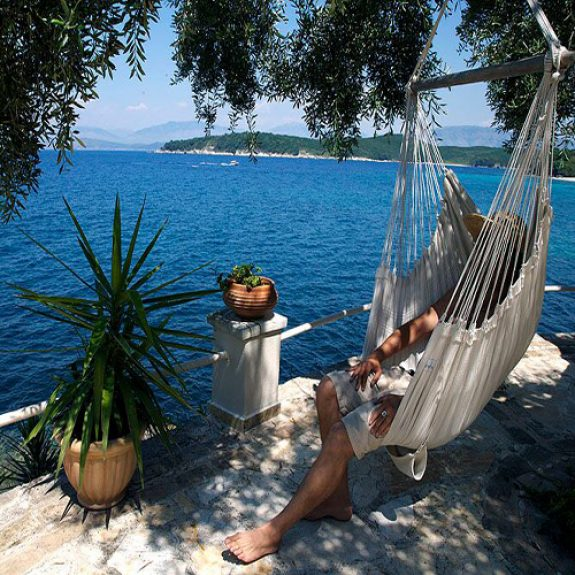 Image of someone sitting in a hammock reading a book at Serenity House, Corfu. The hammock is on a platform by the Ionian Sea, the water is turquoise and inviting