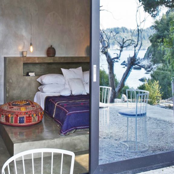 Image of beautiful double bedroom with purple cover, the image is taken from outside, the door is partially closed and the reflection in the door is of the garden and sea behind the photographer. The house is the Secret Beach House in Paxos