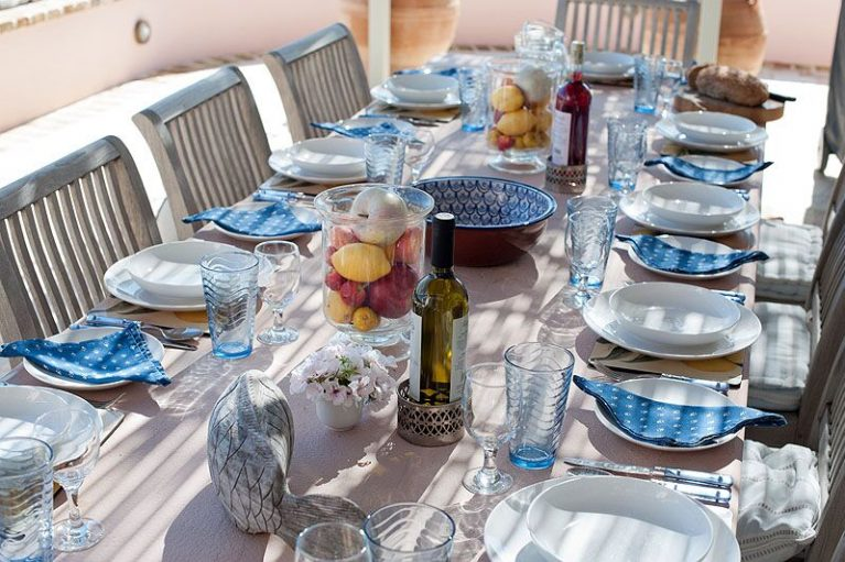 Image of the table at Villa Allanah in Corfu, white plates, blue napkins, all in a dappled sunshine on a wooden table with wooden chairs