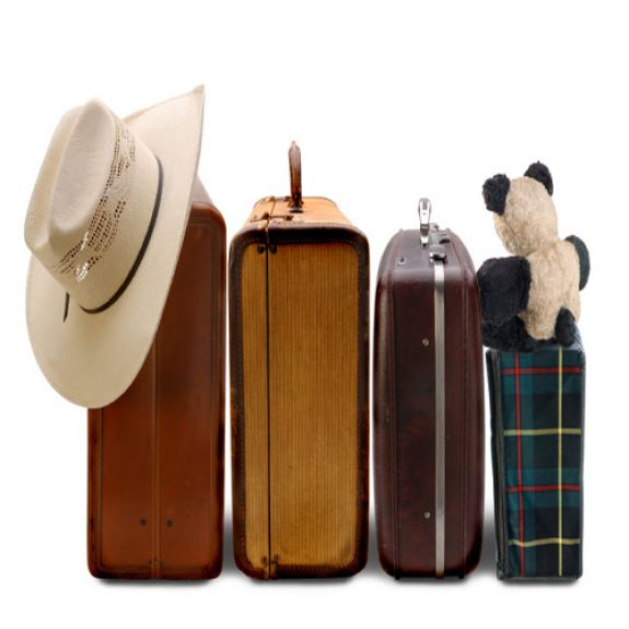 Four suitcases lined up with a teddy bear and a hat balancing on top