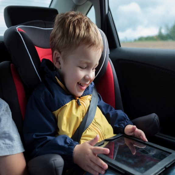 Young boy in his car seat playing on an i pad