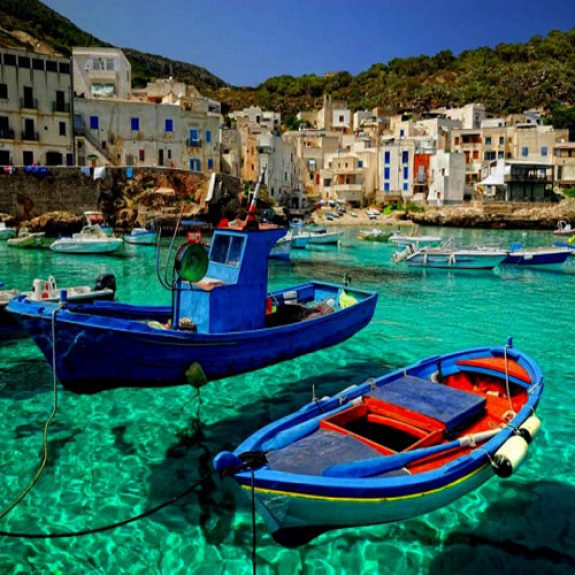 Beautiful blue sea with brightly coloured boats bobbing in the foreground, stunning village in the background - looks like Greece