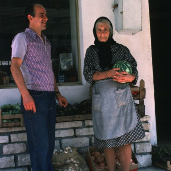 Old lady with black scarf standing by a wall holding a watermelon, younger man standing next to her. Could be Greek?