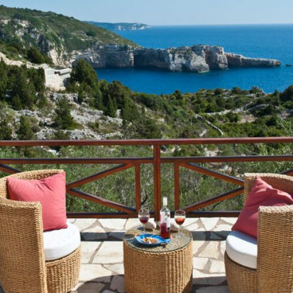 Amazing view of the Ionian sea from Mouzmouli Villa in Paxos. There is a table and two chairs on a balcony with a bottle of rose and glasses