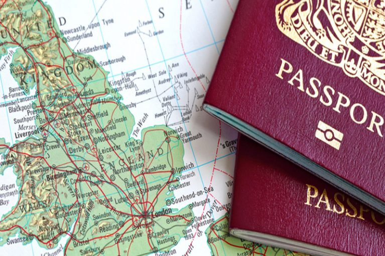 Image of two british passports sitting on top of a map