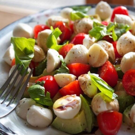 Image of tomato, mozarella and avocado salad with basil leaves on top - on a white plate, looks delicious!