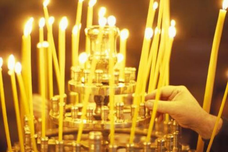 An image of candles in a church - someone is lighting the candles, lots of long, tall, beautiful wax throwing off stunning light