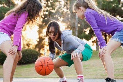 Woman playing basketball with girls on court
