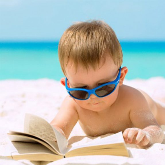 Cute baby boy with sunglasses lying on white sandy beach reading the book and having his first tropical vacation.