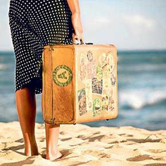 Young woman with suitcase at beach