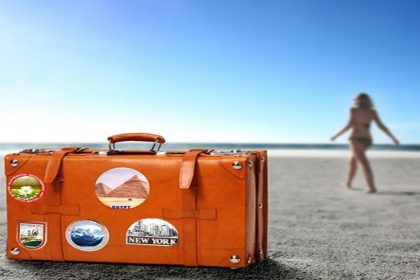 Woman and a suitcase on a beach.