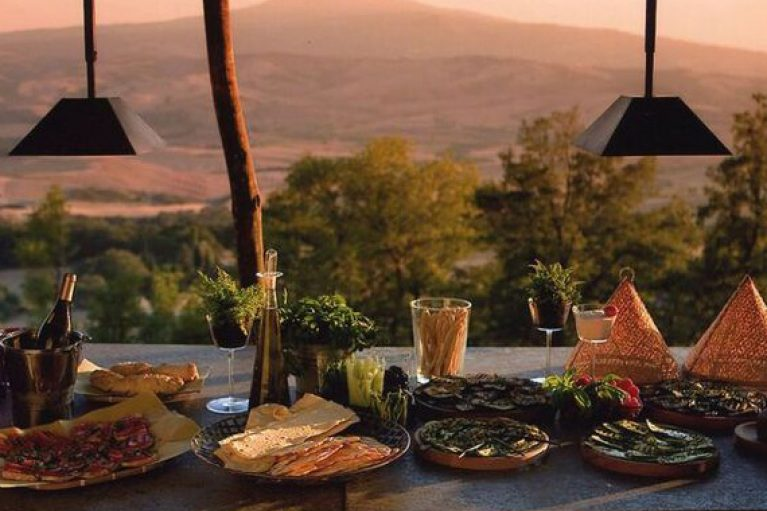 View of the Tuscan hills with delicious food and drinks on a table in the foreground
