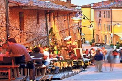 Evening scene in a buzzy, lively Italian town - a scene of people walking up a hill past others eating and drinking outside bars and restaurants
