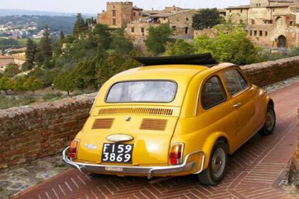 Yellow fiat driving up a terracotta road with beautiful stone houses in background